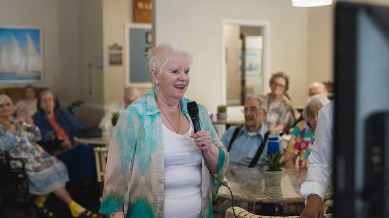 Senior woman holding a microphone talking to a room full of assisted living residents