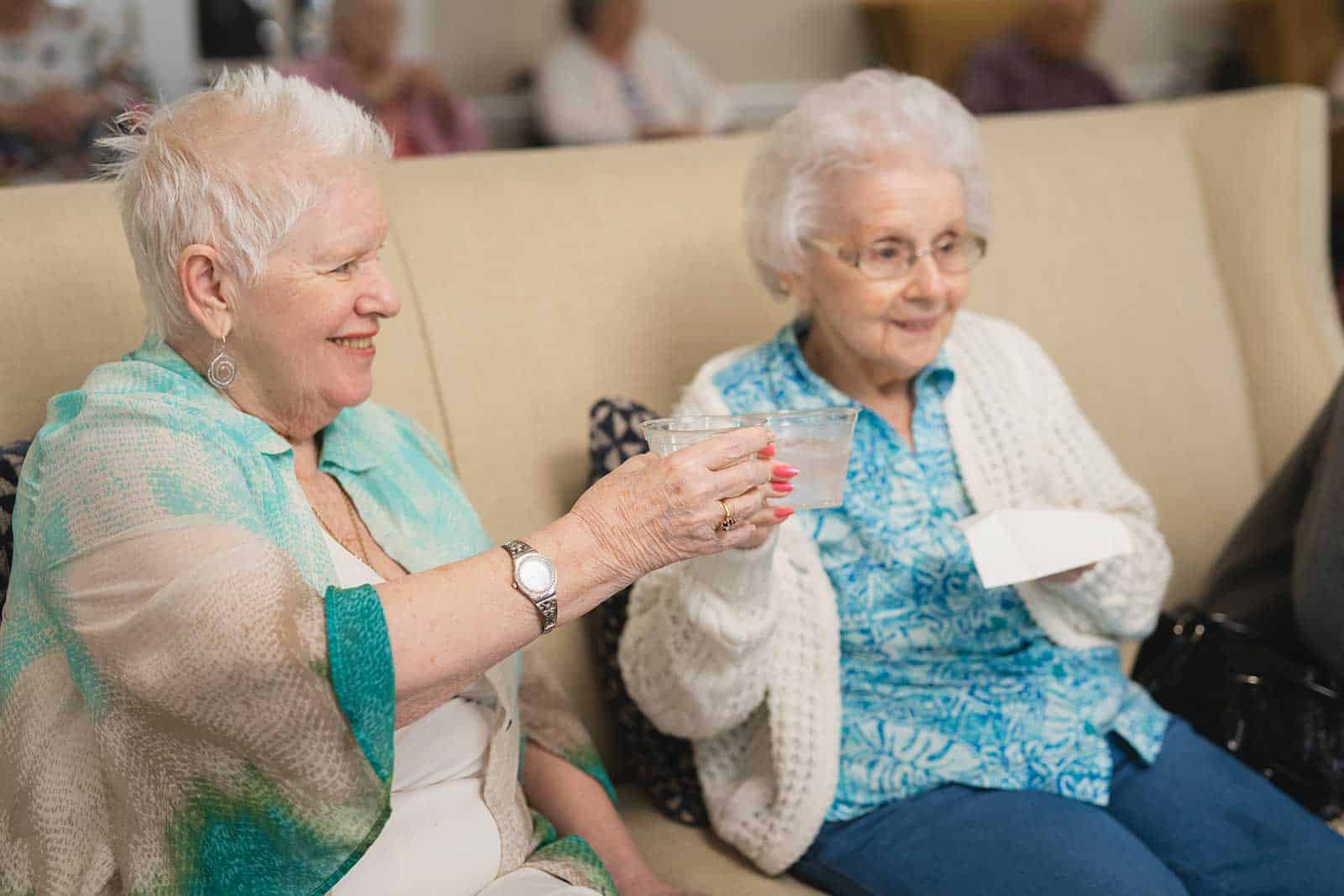 Two senior women tapping cups during happy hour in assisted living community