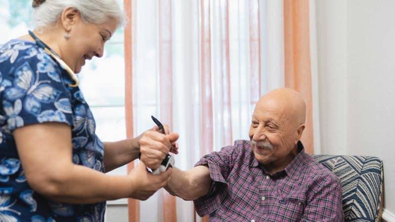 Nurse taking senior man blood pressure in assisted living community
