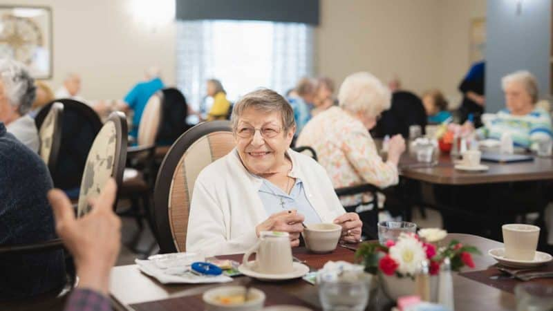 Senior woman seated at table in assisted living dining room talking with dining staff